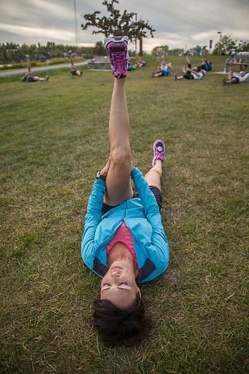 Elizabeth Hooper stretches with members of the Skinny Raven Running Group at Westchester Lagoon, Anchorage  elizabeth@alaska.net (© Clark James Mishler)