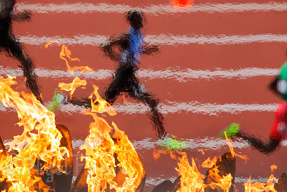 09 AUG 2012 - LONDON, GBR - Nijel Amos (BOT) (centre) of Botswana races  past the Olympic Flame at the start of the men's 800m final at the London 2012 Olympic Games athletics in the Olympic Stadium, Stratford, London, Great Britain .(PHOTO (C) 2012 NIGEL FARROW) (NIGEL FARROW/(C) 2012 NIGEL FARROW)
