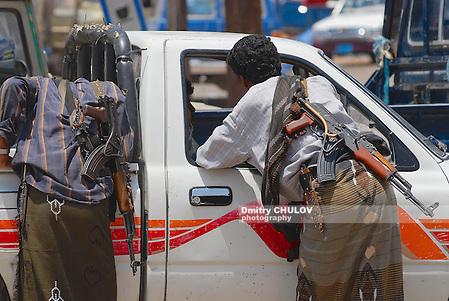 ADEN, YEMEN - SEPTEMBER 14, 2006: Unidentified Yemeni people with Kalashnikov machine guns talk to a car driver on September 14, 2006 in Aden, Yemen. (Dmitry Chulov)
