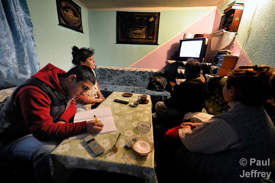 Bajram Kruezi does his homework while his family watches television in their home in the Zemun Polje neighborhood of Belgrade, Serbia. Kruezi attends the Branko Pesic School, an educational center for Roma children and families which is supported by Church World Service. Kruezi's family came to Belgrade as refugees from Kosovo, and like many Roma can't afford regular school fees. Many Roma also lack legal status in Serbia, and thus have difficulty obtaining formal employment and accessing government services. Kruezi wants to be a Muslim religious scholar when he grows up.