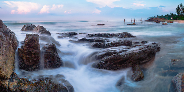 Panoramic photo of stilt fishermen at sunrise at Midigama near Weligama, South Coast, Sri Lanka, Asia. This is a panoramic photo of a stilt fishermen at sunrise at Midigama near Weligama on the South Coast of Sri Lanka, Asia. These stilt fishermen are continuing a tradition that goes back centuries.