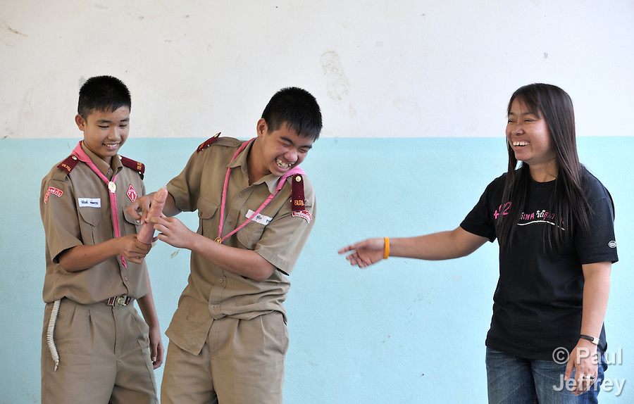 "Wearing their scouting uniforms, children in the village of Toong-sa-tok in northern Thailand learn about HIV and AIDS during a session at the temple-supported Banhuarin School. Helping teach the class is Srisangwan Punyapeng (right), an HIV positive woman who works with Jai-Kao-Jai-Rao (the "" Let's Talk About HIV"" Association) doing public education. Here she helps two boys learn how to properly use a condom."