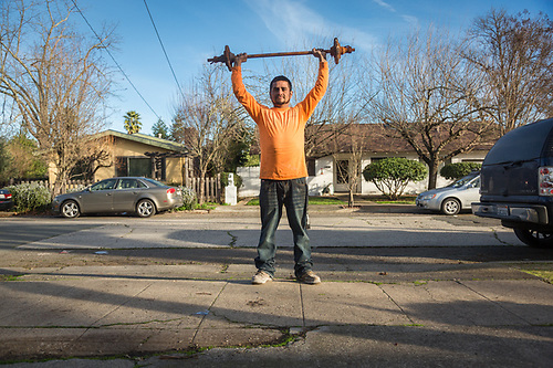 """I work seven days a week clearing burned out properties in Sonoma.  Today, I saved this from the dump truck.  I hope to begin working out just as soon as we are finished working so hard.""  -Edwardo Marin lifts his dumbbell at his home in Calistoga. (Clark James Mishler)"