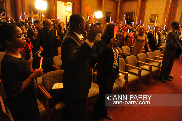 January 11, 2012 - Brooklyn, New York, USA: Commemorating the 2nd anniversary of the Mw 7.0 earthquake in Haiti, people hold up glo-sticks at 2nd Annual Interfaith Memorial Service for Haiti, Wednesday night at Brooklyn Borough Hall. (Ann E Parry/Ann Parry, ann-parry.com)