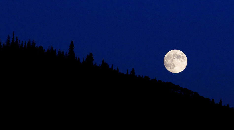 A full moon rises over a mountainside in Steamboat Springs, Colorado. (Christopher Gannon)