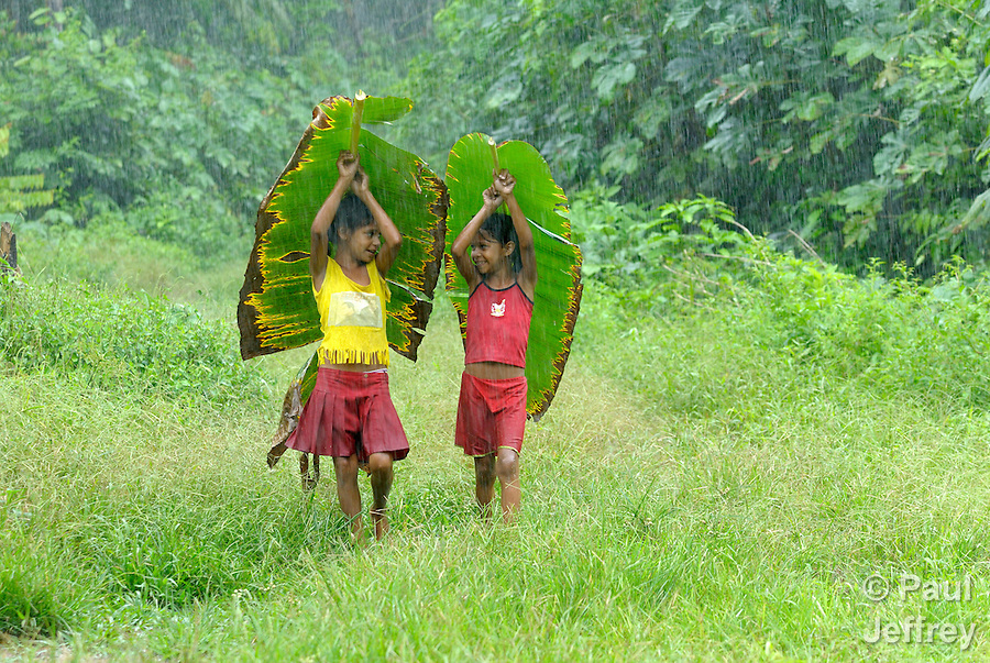 Vanesa Silva de Soza (left) and Yulimara Machin da Silva, both 8, in the rain in the Esperança Sustainable Development Project, where Sister Dorothy Stang, a U.S. nun, was murdered for her defense of the forest and the landless poor. .