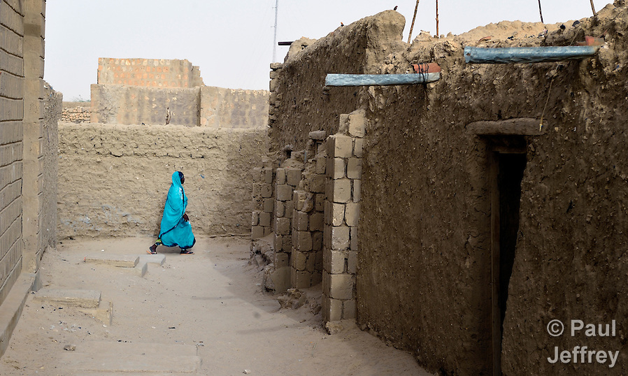 A woman walks along a street in Timbuktu, the northern Mali city that was seized by Islamist fighters in 2012 and then liberated by French and Malian soldiers in early 2013. During jihadist rule, women and girls were not permitted in public unless they were completely covered. (Paul Jeffrey)