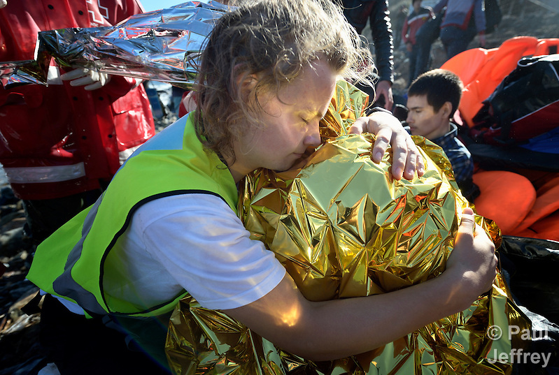 Tordar Tommervik (left), a volunteer from Norway, hugs a cold and frightened Afghan refugee boy on a beach near Molyvos, on the Greek island of Lesbos, on November 2, 2015. The boy was on a boat full of refugees that traveled to Lesbos from Turkey, provided by Turkish traffickers to whom the refugees paid huge sums to arrive in Greece. Tommervik is one of hundreds of volunteers on the island who receive the refugees and provide them with warm clothing and medical care before they continue their journey toward western Europe. (Paul Jeffrey)