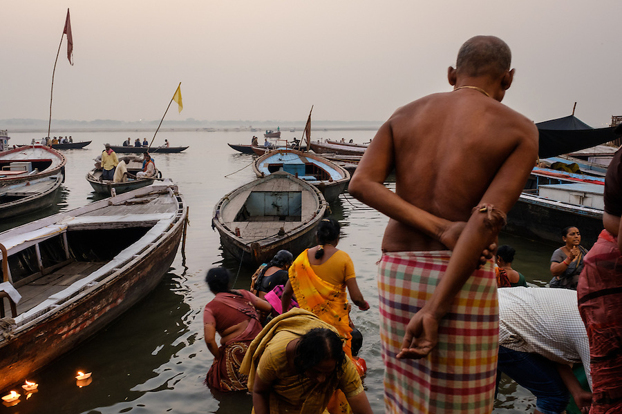 VARANASI, INDIA - CIRCA NOVEMBER 2016: People worshiping and bathing in the Ganges river. Varanasi is the spiritual capital of India, the holiest of the seven sacred cities and with that many rituals and offerings are performed daily by priests and hindus. (Daniel Korzeniewski)