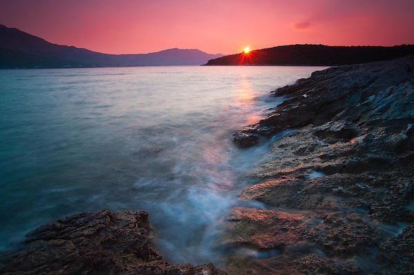 Photo of a sunstar at sunrise in Korcula Town, Korcula Island, Dalmatian Coast, Croatia, Europe. This photo shows a sunstar at sunrise, taken just a short walk along the rocky Dalmatian Coast from Korcula. Korcula is the main town on Korcula Island and is a stunning example of a traditional old Croatian coastal town.