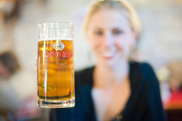Photo of a tourist drinking Karlovacko Beer, Trogir, Dalmatian Coast, Croatia. This photo shows a large glass of Karlovacko beer, easily the most popular along the Dalmatian Coast of Croatia.