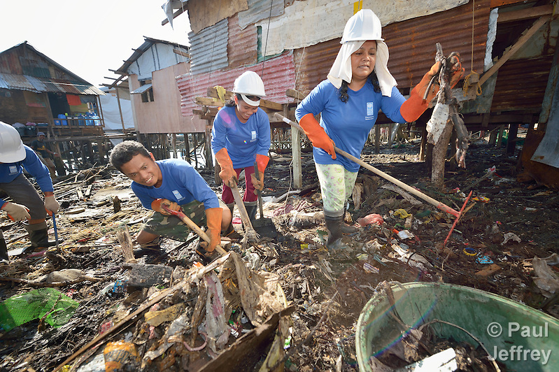 Participants in a cash for work program clean up debris in Tacloban, a city in the Philippines province of Leyte that was hit hard by Typhoon Haiyan in November 2013. The storm was known locally as Yolanda. The ACT Alliance has been active here and in affected communities throughout the region helping survivors to rebuild their homes and recover their livelihoods. (Paul Jeffrey)
