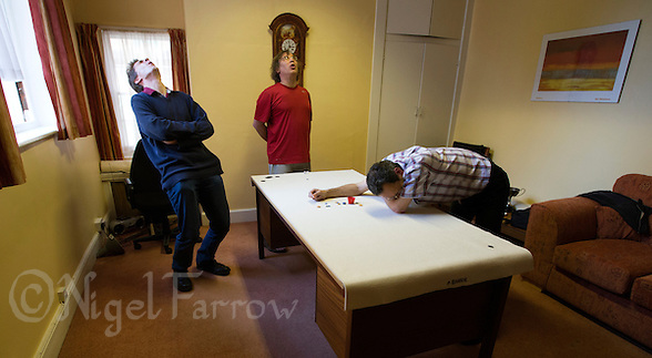 24 OCT 2013 - CAMBRIDGE, GBR - Challenger Patrick Barrie (GBR) (right) of Great Britain rues a missed pot watched by title holder Larry Kahn (USA) (centre) of the USA and umpire Matt Fayers (left) during tiddlywinks World Singles 67 in Barrie's office at Emmanuel College, Cambridge, Great Britain. Barrie who took up the sport as an undergraduate at the university in 1984 now lectures in Chemical Engineering there (PHOTO COPYRIGHT © 2013 NIGEL FARROW, ALL RIGHTS RESERVED) (NIGEL FARROW/COPYRIGHT © 2013 NIGEL FARROW : www.nigelfarrow.com)