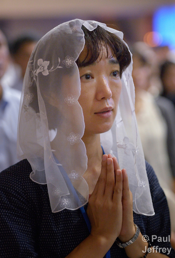 A woman prays during a special mass for peace in the Urakami Cathedral in Nagasaki, Japan, on August 9, 2015, the 70th anniversary of the day the United States dropped an atomic bomb on the city. The Catholic cathedral was destroyed by the bombing and rebuilt years later. (Paul Jeffrey)