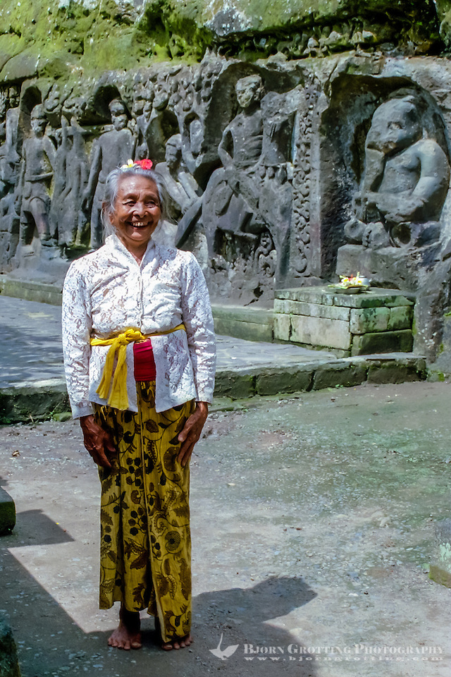 Bali, Gianyar, Yeh Pulu. A Pemangku, a holy old woman who watches over and maintains the site. Behind her the statue of Ganesh with the elephant head. (Photo Bjorn Grotting)