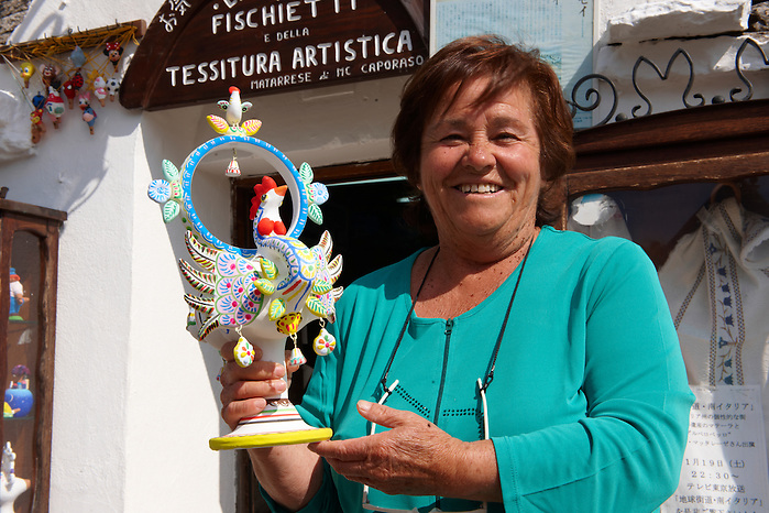 Trulli whistle shop La Botega die Finchietti, with owner Anna Marie  Matarrese holding an ornate folk decorated whistle.  Alberobello, Puglia, Italy.  Pictures, photos, images & fotos. (By Travel photographer Paul Williams. http://www.funkystock.eu)