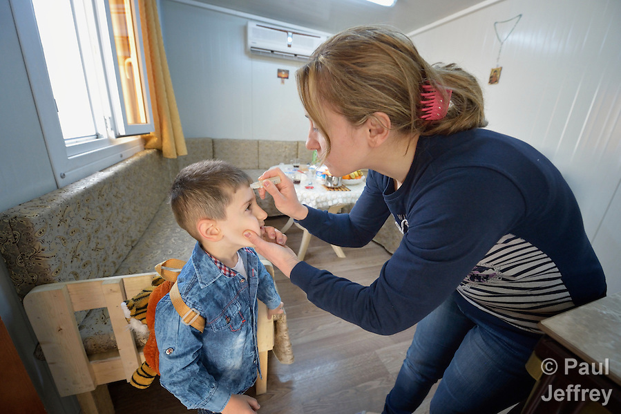 Every morning in Ankawa, Iraq, as her 4-year old son Luis prepares to leave for preschool, Raeda Firas takes a stick of oil and makes the sign of the cross on his forehead. The Christian family was displaced from Mosul by ISIS in 2014, and lives in a church-provided modular home. (Paul Jeffrey)