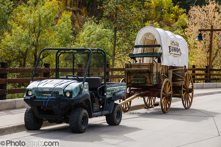 A modern vehicle pulls a covered wagon in Deadwood, Lawrence County, South Dakota.  (© Tom Dempsey / PhotoSeek.com)