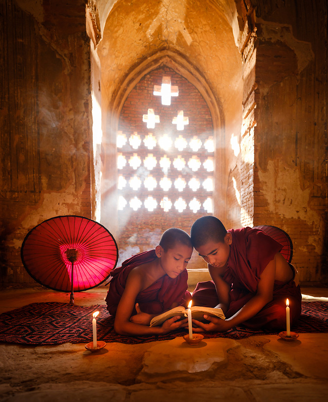 BAGAN, MYANMAR - CIRCA DECEMBER 2017: Monks inside a temple reading a book around candelights on a temple in Bagan (Daniel Korzeniewski)