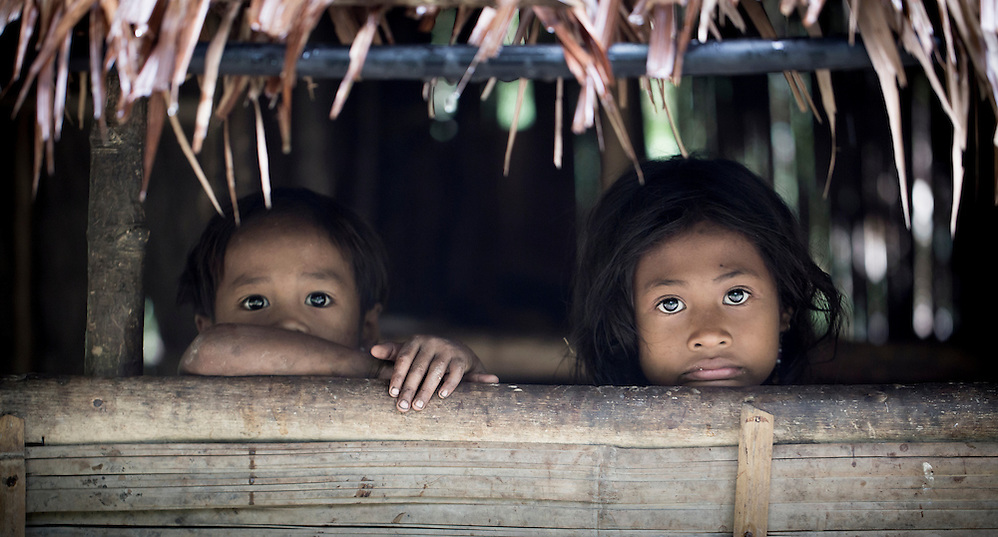A girl and boy peer out from their hut in a Batak village in Palawan, the Philippines (Robin Moore)