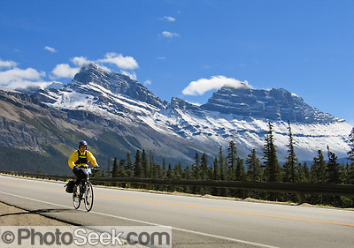 A bicyclist zooms down Icefields Parkway south of Sunwapta Pass in Banff National Park, Alberta, Canada.