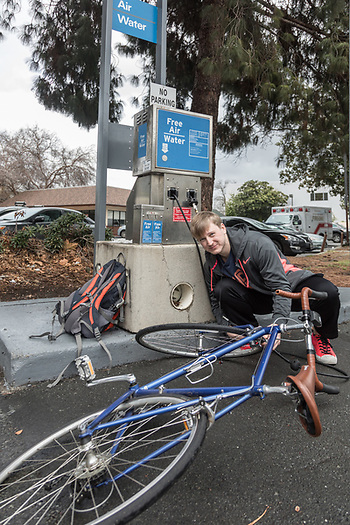Indoor cycling facility coordinator Andrew Alfieri pumps up his bicycle tire in Concord, CA. (© 2017 Clark James Mishler)