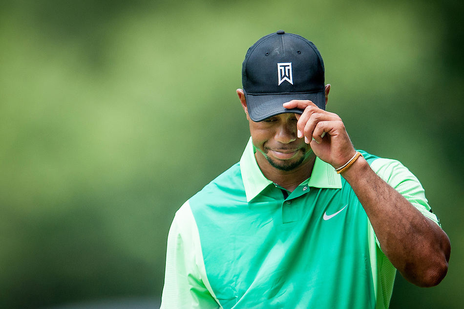 Tiger Woods acknowledges the gallery after tapping in for par on the 6th hole during the first round of the Quicken Loans National golf tournament on Wednesday at Congressional Country Club in Bethesda, Maryland. This marked  Woods' return to competition for the first time in three months after having surgery just a week before the Masters in April of this year. (Pete Marovich/Corbis)