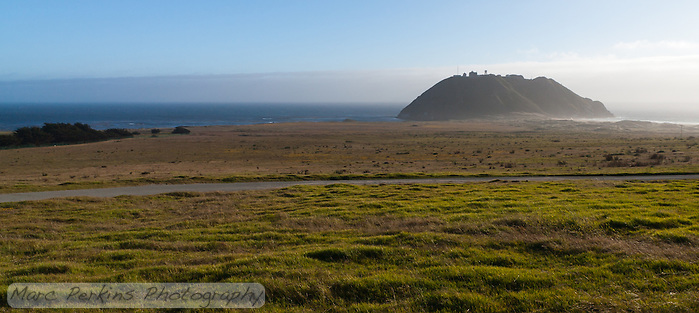 Point Sur Light Station seen from along California Highway 1 (Pacific Coast Highway).  The station's buildings are all on top of the small hill / rock that rises from the ocean behind a grassy meadow on this blustery day. (Marc C. Perkins)