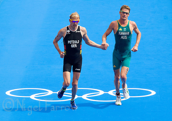 07 AUG 2012 - LONDON, GBR - Maik Petzold (GER) of Germany (left) and Brad Kahlefeldt (AUS) of Australia (right) help each other to the finish line at the end of the men's London 2012 Olympic Games Triathlon in Hyde Park in London, Great Britain .(PHOTO (C) 2012 NIGEL FARROW) (NIGEL FARROW/(C) 2012 NIGEL FARROW)
