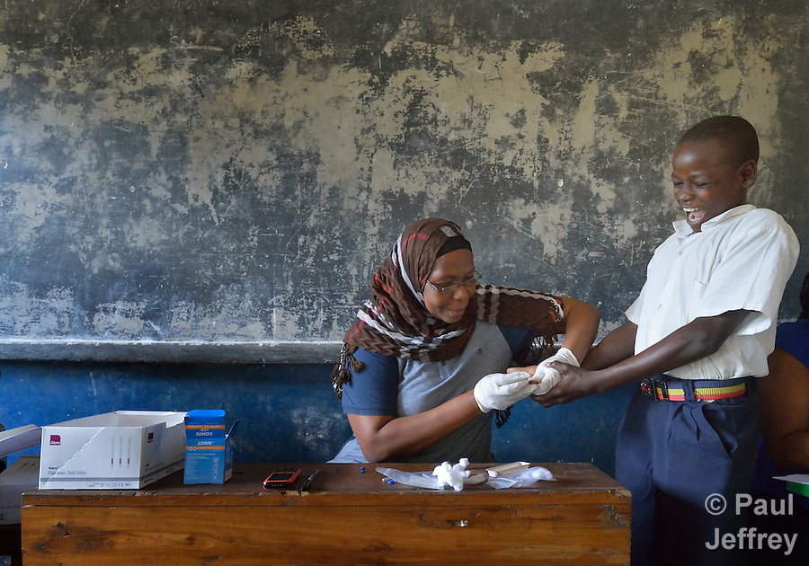 Testing for Lymphatic filariasis, Mwanaidi Mtui takes a blood sample from a boy in a public school in Vikuge, Tanzania. (Paul Jeffrey)
