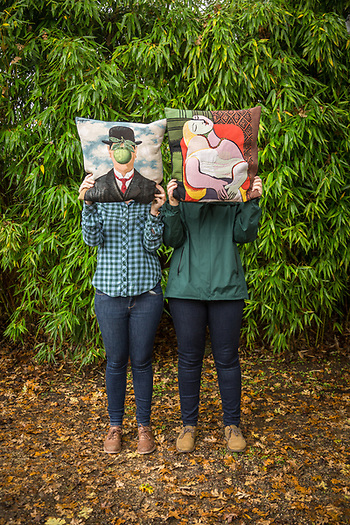 Two women holding Magritte and Picasso pillows, Calistoga (Clark James Mishler)