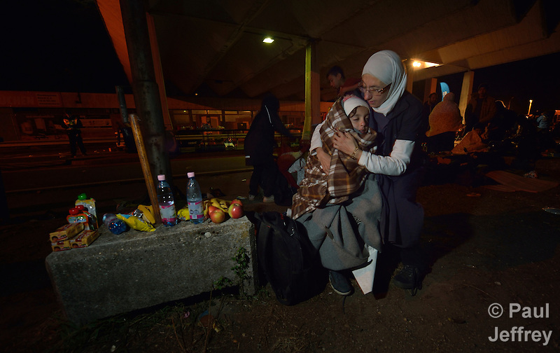 """Mayada Ari was a math teacher in Deir ez-Zor, Syria, when the fighting caused her eyesight to deteriorate, and she was constantly afraid for her children. So she and her husband and their four kids set off for western Europe. """"We heard that the best life is in Germany,"""" she said. They traversed Turkey and Greece and Macedonia and Serbia until arriving in Hungary. She said the journey has been difficult and dangerous. """"But it was more dangerous to remain at home,"""" she said. In this image, she cuddles a daughter as they shiver in the cold night air as the family leaves the Hungarian town of Hegyeshalom and prepares to cross the border into Austria. At the border crossing, she and her family received food and blankets from Hungarian Interchurch Aid, a member of the ACT Alliance. Hundreds of thousands of refugees and migrants flowed through Hungary in 2015, on their way to western Europe from Syria, Iraq and other countries. (Paul Jeffrey)"""