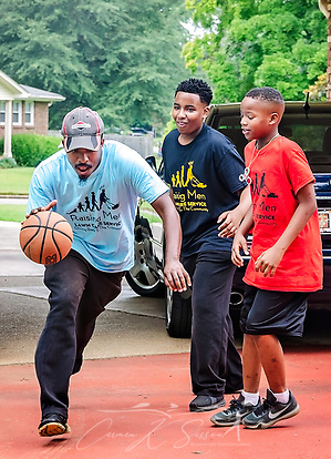 Rodney Smith Jr. dribbles a basketball as Lamar Knight and Quay Knight watch, Aug. 1, 2018, in Huntsville, Ala. The boys are among more than 250 youth cutting grass as part of Raising Men Lawn Care Service, a non-profit organization Smith founded which provides free lawn care for the elderly, disabled, veterans, and single mothers. (Photo by Carmen K. Sisson) (Carmen K. Sisson/Cloudybright)