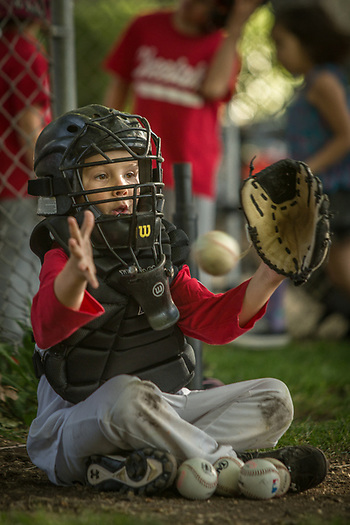 Six year old Tommy Garrett of the Saint Helena Volcanoes catches against the Calistoga Cheetahs at Calistoga Elementary School. (Clark James Mishler)