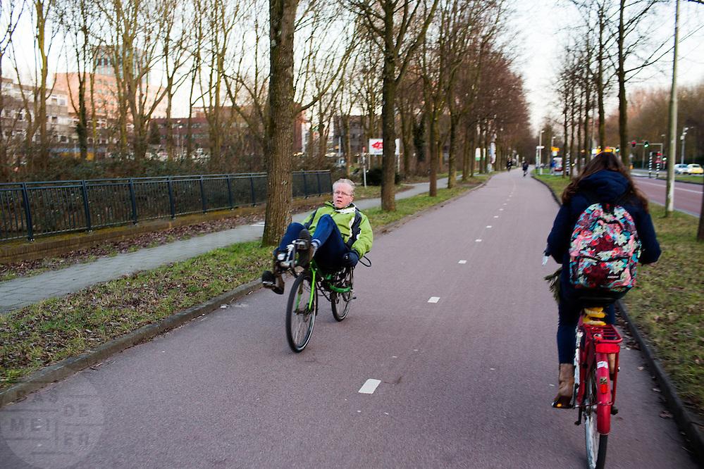 In Utrecht fietst een man op een groene ligfiets over het fietspad bij bedrijventerrein Rijnsweerd.