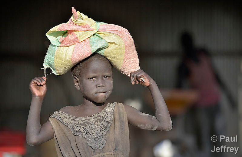 Wunrock Langar carries home sorghum meal from a Caritas-sponsored grinding mill run by widows in a displaced persons camp in Agok, South Sudan. Tens of thousands of residents of Abyei, a contested region along the border between Sudan and South Sudan, remain displaced in Agok. Under a 2005 peace agreement, Abyei was supposed to have a referendum to decide which country it would join, but the two countries have yet to agree on who can vote. In 2011, militias aligned with Khartoum drove out most of Abyei's Dinka Ngok residents, pushing them across a river into Agok. More than 40,000 Dinka Ngok have since returned to Abyei with support from Caritas South Sudan, which has drilled wells, built houses, opened clinics and provided seeds and tools for the returnees. Yet continuing insecurity means a greater number remain in Agok, where they remain dependant on Caritas and other organizations for food and other support. (Paul Jeffrey)