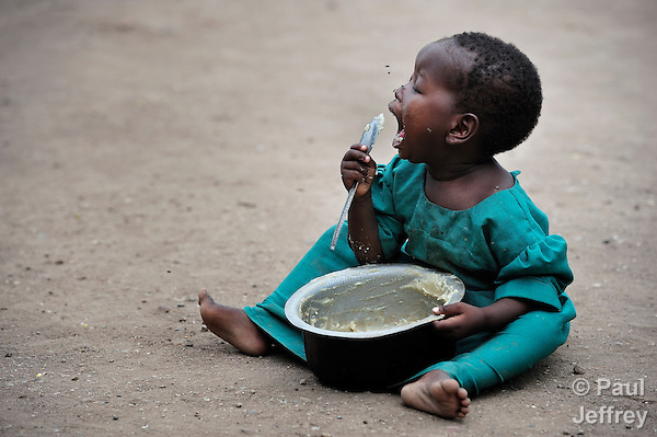 A girl eats sorghum porridge as she sits in the dirt in Chidyamanga, a village in southern Malawi that has been hard hit by drought in recent years, leading to chronic food insecurity, especially during the