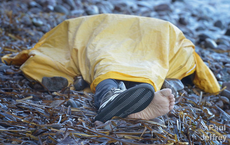 The body of a refugee child lies on a beach on the Greek island of Lesbos on November 1, 2015. It was covered with a plastic raincoat by Spanish lifeguards until it could be picked up by local authorities. The body appeared to be that of an Afghan boy of about 8 years of age. Thousands of refugees have died this year attempting to cross the Aegean from Turkey to Greece. Fleeing violence in Syria, Iraq, Afghanistan and elsewhere, most are on their way toward western Europe. (Paul Jeffrey)