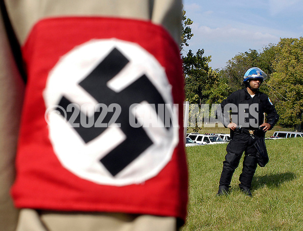 VALLEY FORGE, PA - SEPTEMBER 25: A National Park Police Officer stands guard behind an American Nazi party member during American Nazi Party rally at Valley Forge National Park September 25, 2004 in Valley Forge, Pennsylvania. Hundreds of American Nazis from around the country were expected to attend. (Photo by William Thomas Cain/Getty Images) (William Thomas Cain/Getty Images)