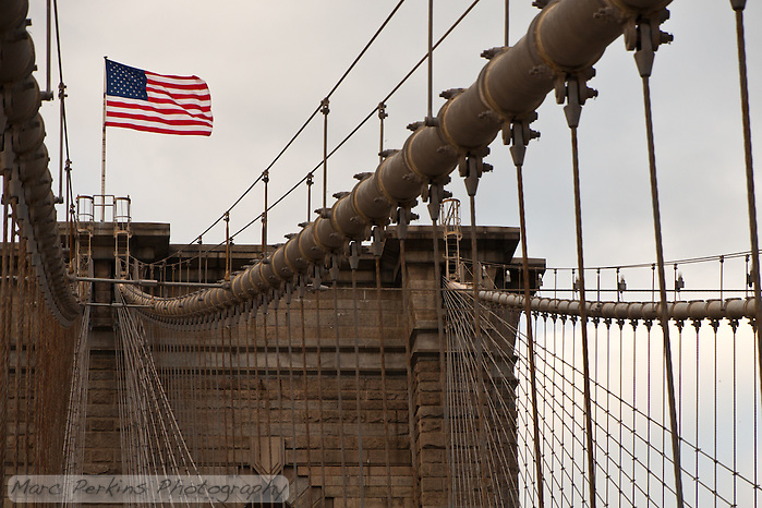 The American Flag waves in a strong wind on top of one of the towers of the Brooklyn Bridge, with patchy clouds behind it.  The tower's central pair of cables and lines angle up to the flag, bringing it to the focus. (Marc C. Perkins)