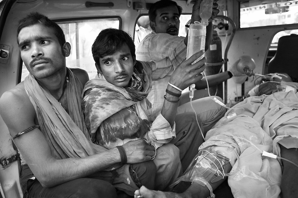 The husband (2nd left) of a 30-year old woman who had attempted suicide looks on anxiously as she is transported by ambulance from the JSS hospital in Ganiyari to the ICU at the large government hospital in Bilaspur, 25km away. The woman is one of many such cases of attempted suicide by the ingestion of insecticide. She was brought to the JSS hospital on a motorbike where doctors spent two hours stabilising her. The woman survived thanks to the efforts of the JSS and was discharged from hospital one week later. ..The JSS (Jan Swasthya Sahyog or People's Health Support Group) is a public-health initiative established in 1996 by a handful of committed doctors all of whom trained at elite medical schools in India. While many of their peers secured high profile, high earning posts in premier hospitals in India, the US and the UK, the doctors at JSS have focussed their medical expertise on providing a service for poor and marginalised rural communities in Bilaspur district in the east Indian state of Chhattisgarh. Relying on grants and private donations, the doctors at JSS pay themselves only Rs.20,000 (US$500) a month...The JSS operate out of a hospital in Ganiyari, 25km from the main district town of Bilaspur. The JSS provide a first-class medical service for a community that would otherwise rely on underfunded and poorly resourced government facilities. Though the hospital at Ganiyari boasts 30 beds, two operating theatres, a fully-equipped lab and three outpatient clinics every week, the service provided by JSS is over-subscribed by a community totaling 800,000 people from 1,500 villages. ..To address the malnutrition that is so widespread among the population they serve, the JSS offers training on new agricultural techniques. The JSS has a well established outreach program of village-clinics and employs over 100 village health workers serving 53 villages. The JSS also operates an ambulance service and assists with transport costs for a rural community who's access t (Tom Pietrasik)