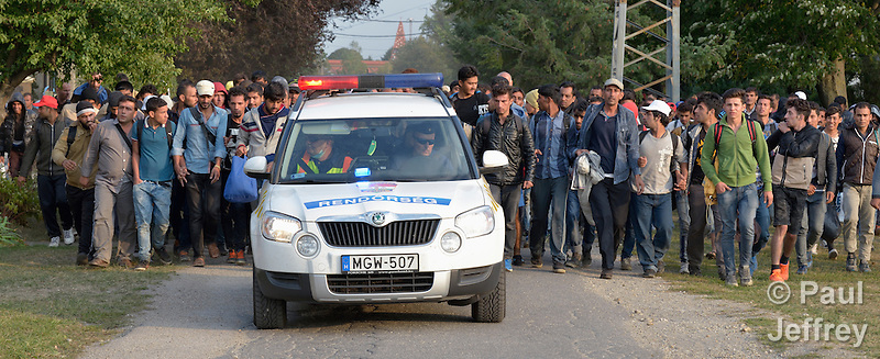 Carefully shepherded by police, refugees and migrants walk through the Hungarian town of Hegyeshalom on their way to the border where they will cross into Austria. Hundreds of thousands of refugees and migrants flowed through Hungary in 2015, on their way from Syria, Iraq and other countries to western Europe. (Paul Jeffrey)