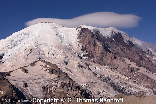 A lenticular cloud forms over the top of Mt Rainier. A landslide came down part of Willis Wall while I was watching. I heard the crack and saw dust rise as the debrey crashed down to the glacier below. (G. Thomas Bancroft)