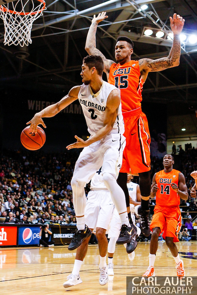 January 2nd, 2014:  Colorado Buffaloes junior guard Askia Booker (0) dishes the ball past Oregon State Beavers junior forward Eric Moreland (15) in the first half of action in the NCAA Basketball game between the Oregon State Beavers and the University of Colorado Buffaloes at the Coors Events Center in Boulder, Colorado (Carl Auer/ZUMAPRESS.com)