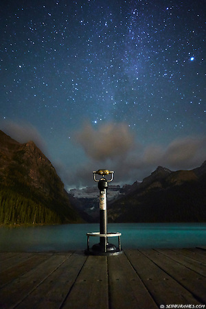 A telescope in the foreground looking up at the Milky Way galaxy in a star-filled night sky. (Seth K Hughes)