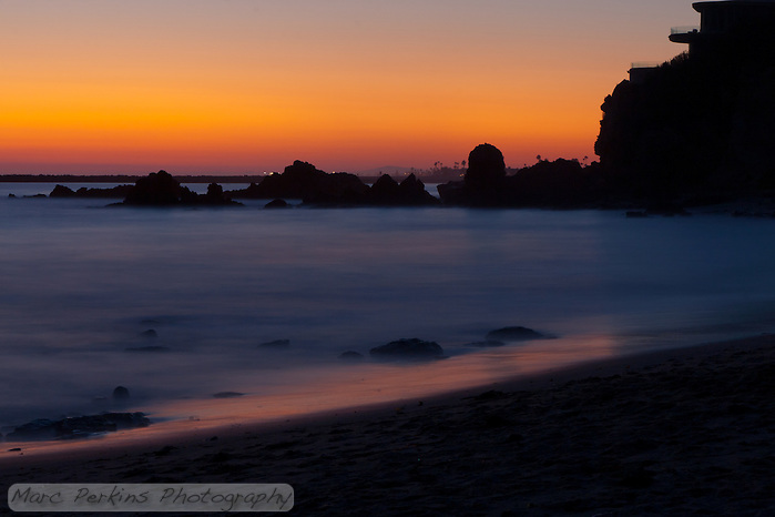 A long-exposure shot taken after sunset at Little Corona beach in Corona Del Mar (Newport Beach), CA.  The rocky line at the horizon is the entrance to Newport Harbor.  There were absolutely no clouds for this sunset, but I love the orange/red hues. (Marc C. Perkins)