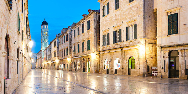 Panoramic photo of the Franciscan Monastery on Stradun, the main street in Dubrovnik Old Town at night, Dalmatia, Croatia, Europe. This panoramic photo shows the Franciscan Monastery and Stadun, the main street in Dubrovnik, completely empty at night. Most of the day, the cobbled limestone street, Franciscan Monastery Museum, Old Town Bell Tower and stunning architecture draw people in their thousands. Unfortunately this means that the only time to see this famous street completely deserted of tourists is at night. Stradun is the central point of Dubrovnik Old Town which is a UNESCO World Heritage Listed Town.