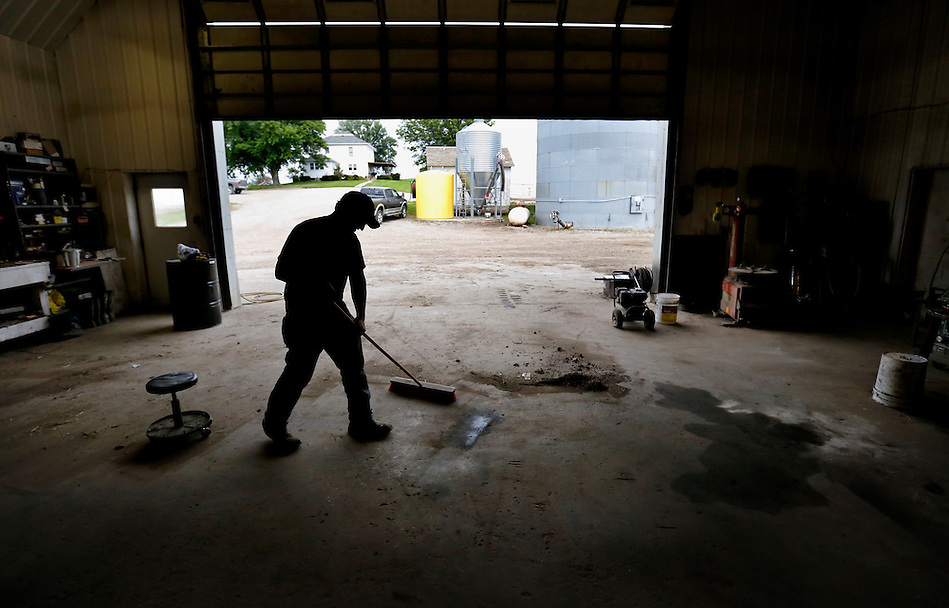 Jordan Dammann, the Dammann Farm's master mechanic, sweeps out his shop at the end of the work day on July 2, 2014. (Christopher Gannon/The Register)