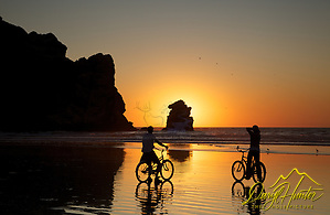 Bicyclers, Beach, sunset, Morro Rock, Morro Bay, California (Daryl Hunter's &quot;The Hole Picture&quot;  Daryl L. Hunter has been photographing the Yellowstone Region since 1987, when he packed up his view camera, Pentex 6X7, and his 35mms and headed to Jackson Hole Wyoming. Besides selling photography Daryl also publ)