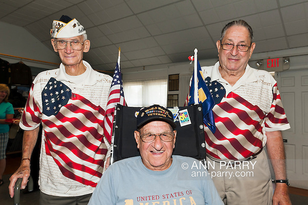 Veterans, including Pearl Harbor survivor Bill Halleran (standing at left), at Merrick Post #1282 of American Legion barbecue hosted for Veterans from New York State Nursing Home at Stony Brook NY, in Merrick, New York, USA, on August, 13, 2011. American Legion vetearns standing wearing shirts with big American flag on them, and WWII Veteran in middle is wheelchair decorated with American flags. NOTE: EDITORIAL USE ONLY. RESTRICTIONS also include image is NOT for use for Sensitive Issues, Nor Religious issues, nor Political Issues. (Ann Parry/© Ann Parry, Ann-Parry.com)